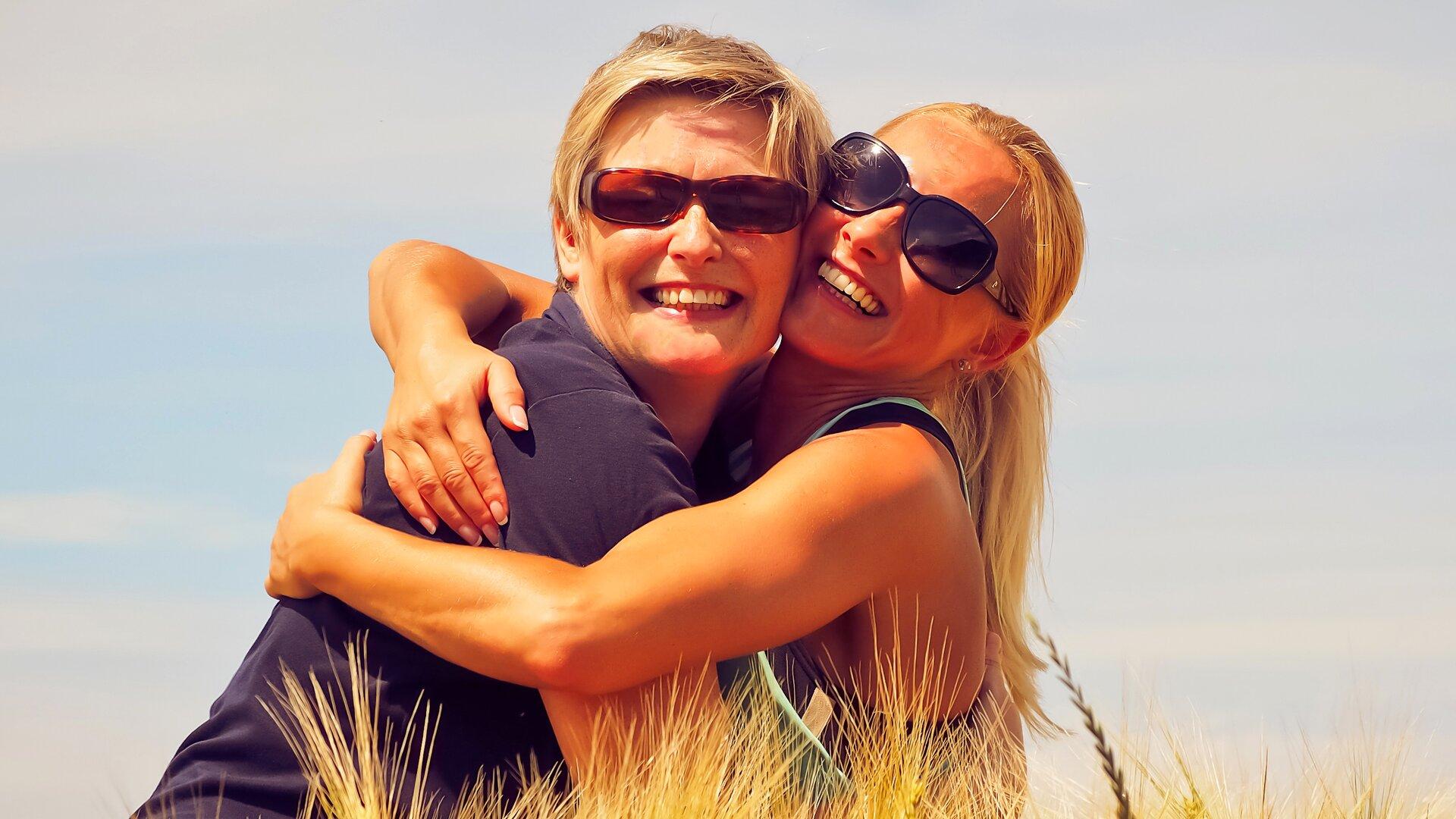 Ilustracja przedstawia dwie, uśmiechnięte kobiety ściskające się na łące. Obie mają włosy wkolorze blond ipodobne rysy twarzy. Kobieta znajdująca się po lewej stronie fotografii jest starsza. Prawdopodobnie to matka zcórką. Jest letni, słoneczny dzień. Wskazuje na to garderoba obu pań.