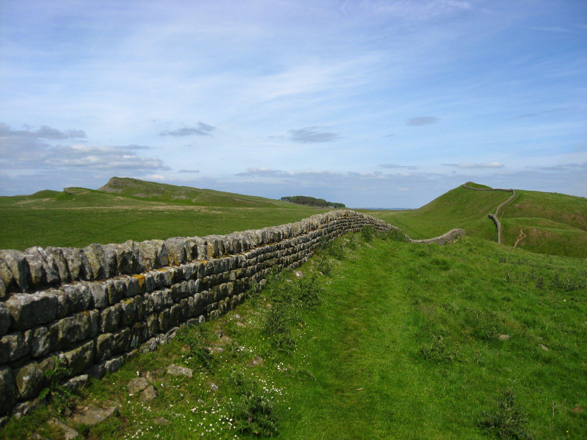 Na zdjęciu kamienny mur ciągnący się przez rozległe pagórkowate tereny.