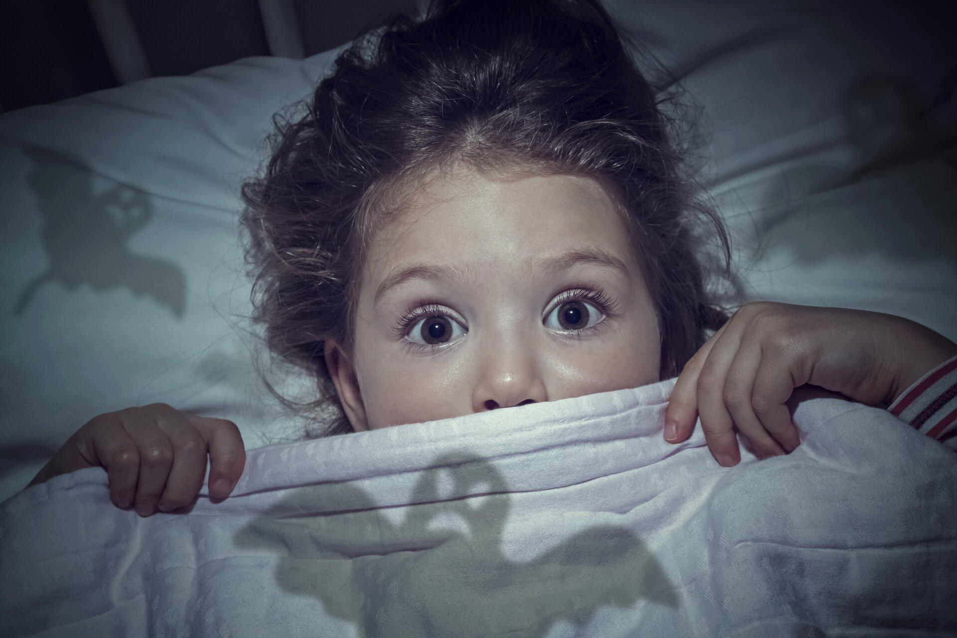 Ilustracja przedstawia przestraszoną dziewczynkę.