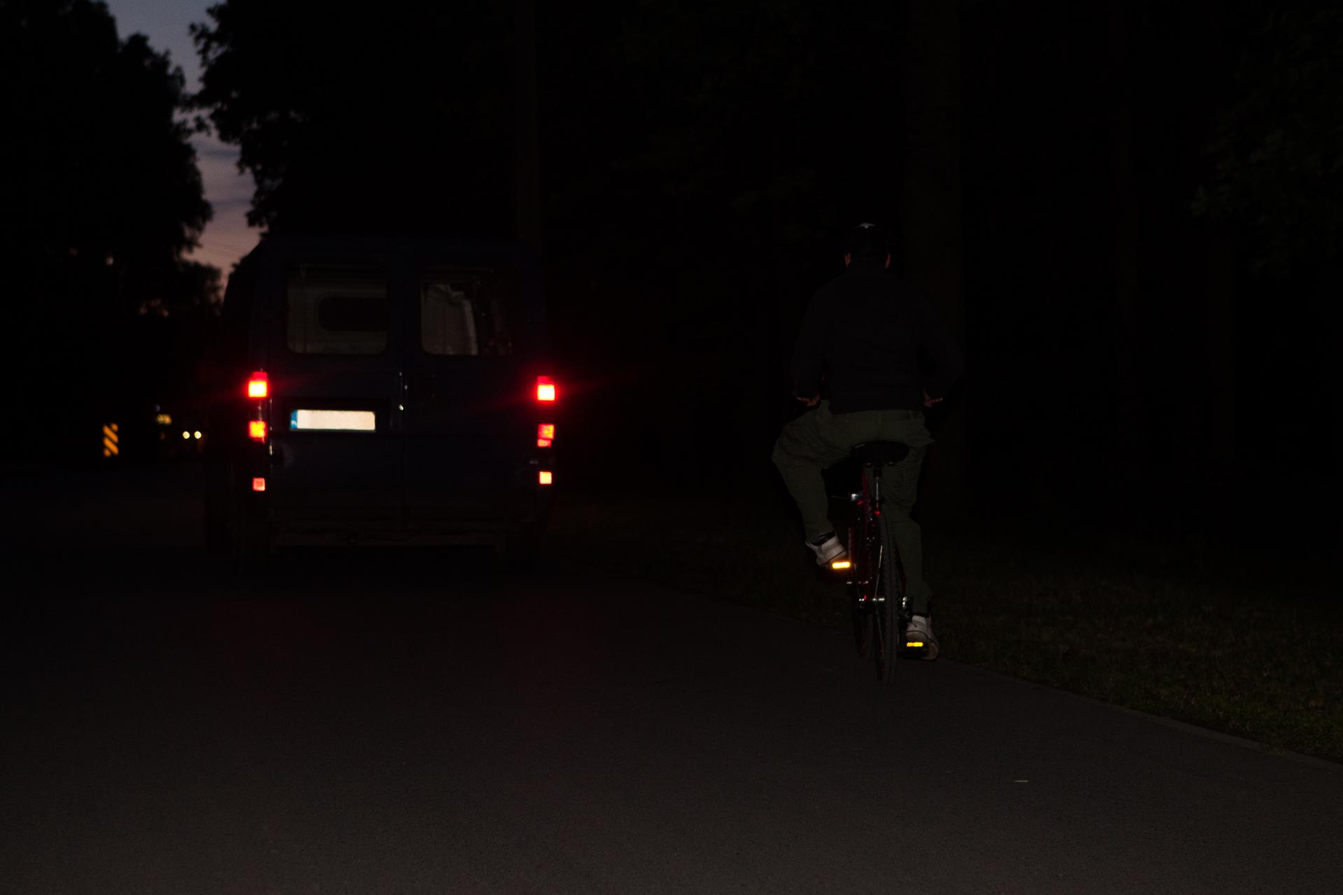 Rowerzysta nocą bez elementów odblaskowych, prawie niewidoczny