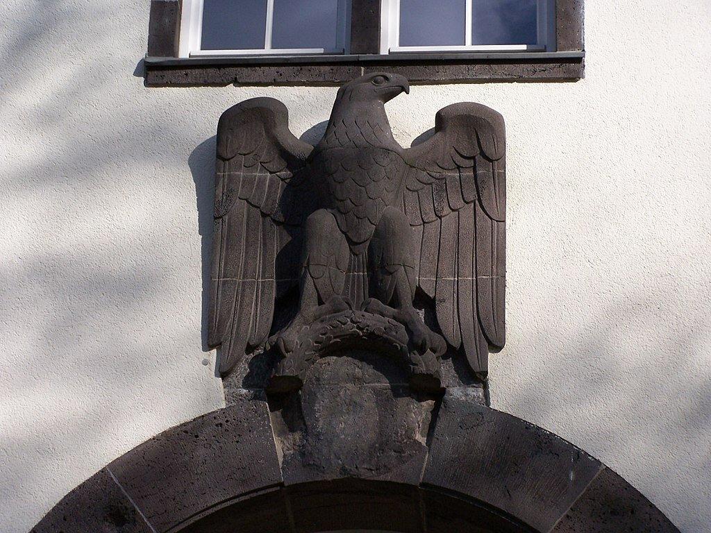 Orzeł nad wejściem do jednego zbudynków Uniwersytetu Technicznego wDarmstadt, widok współczesny. Zwróć uwagę na puste miejsce pod orłem – wramach denazyfikacji usunięto zniego swastykę.