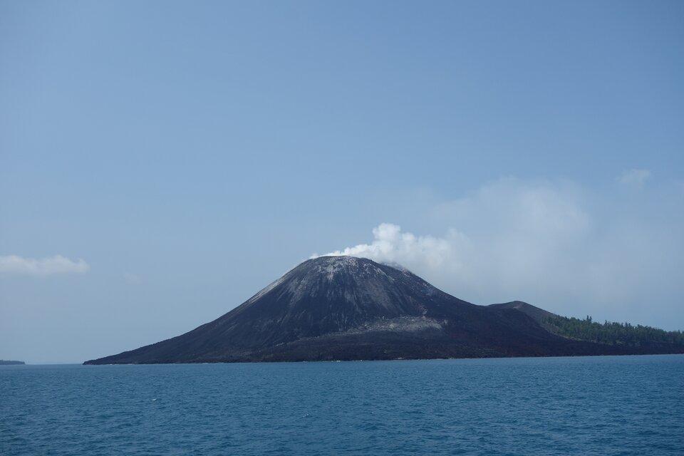 Na zdjęciu wulkan, zkrateru wydobywa się dym. Na pierwszym planie woda.