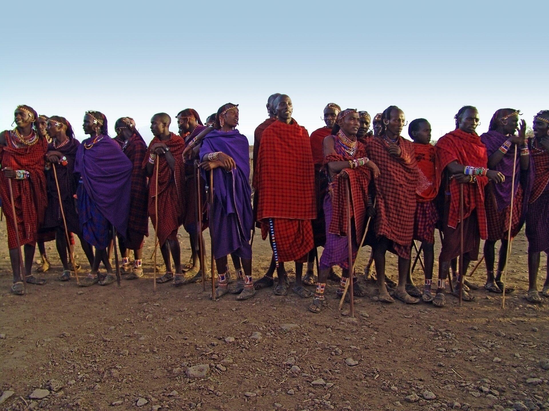 Fotografia przedstawia grupę masajskich wojowników. Mężczyźni mają ciemną skórę, są owinięci kolorowymi tkaninami – brązowymi, czerwonymi, wkratę. Wielu trzyma wrękach kije lub opiera się na nich. Mają pomalowane twarze iozdoby na krótkich włosach. Na nogach sandały iopaski. Ludzie ci są uśmiechnięci, rozmawiają ze sobą.
