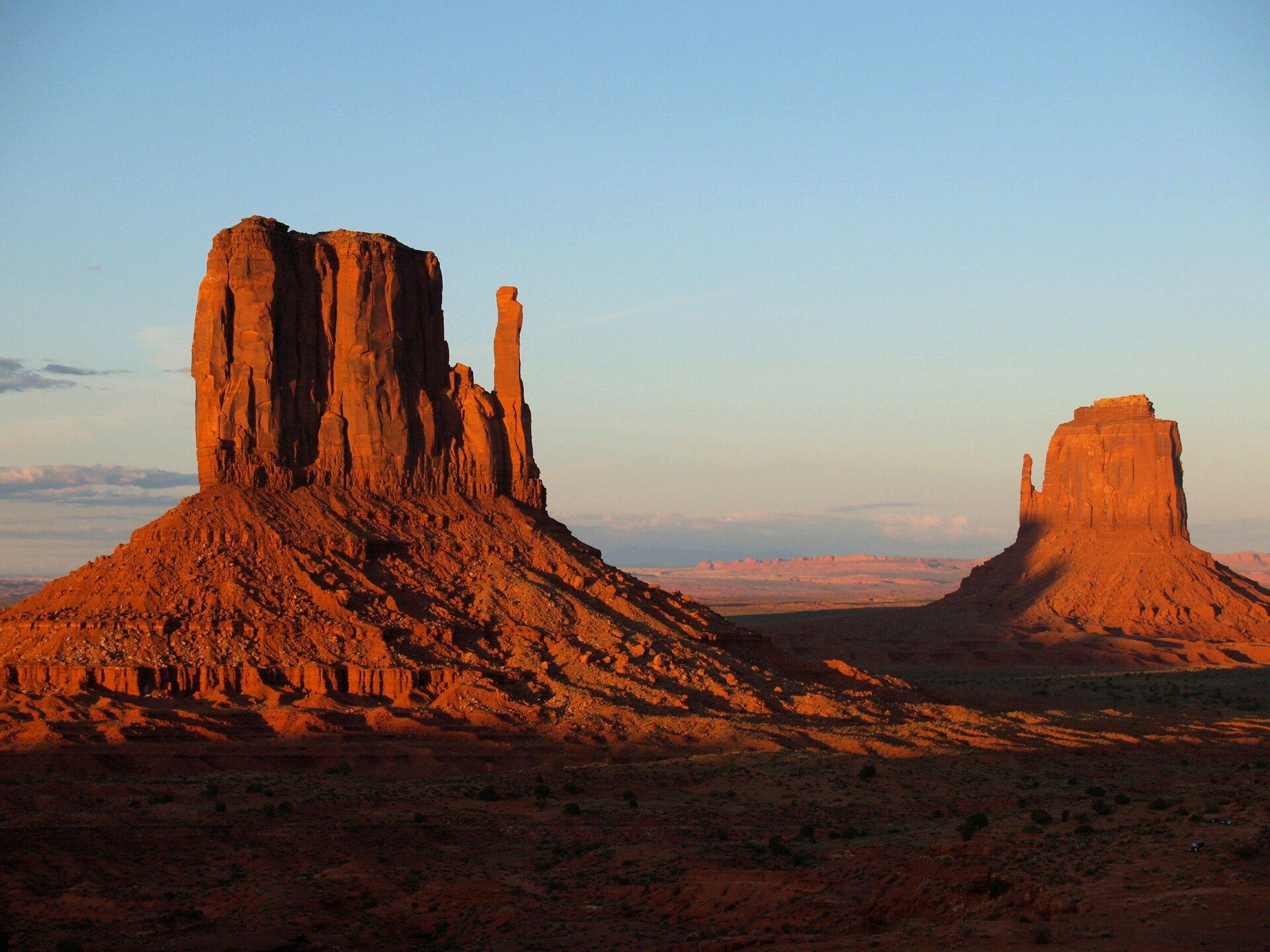 Fotografia prezentuje pustynię skalistą wMonument Valley wUSA. Na pierwszym planie widoczne dwie wysokie, prostokątne góry upodstawy, których znajdują się zwietrzałe okruchy skalne. Skały są koloru czerwonego.