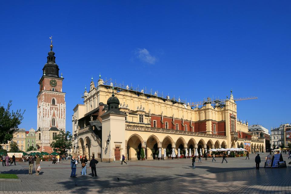 Fotografia zKrakowa, widoczny rynek Starego Miasta zSukiennicami iwieżą Ratuszową.