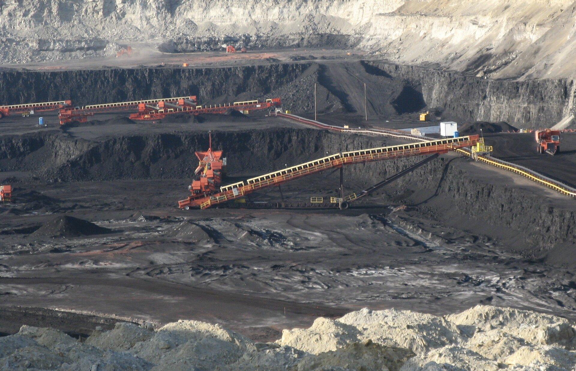 Na zdjęciu kopalnia odkrywkowa. Głębokie wykopy. Taśmociągi do podawania węgla. Maszyny iurządzenia górnicze.