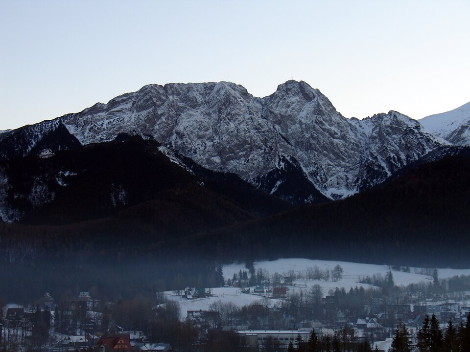 Na zdjęciu stromy, skalisty szczyt górski pokryty śniegiem. Wdole ustóp gór zabudowanie miejskie.