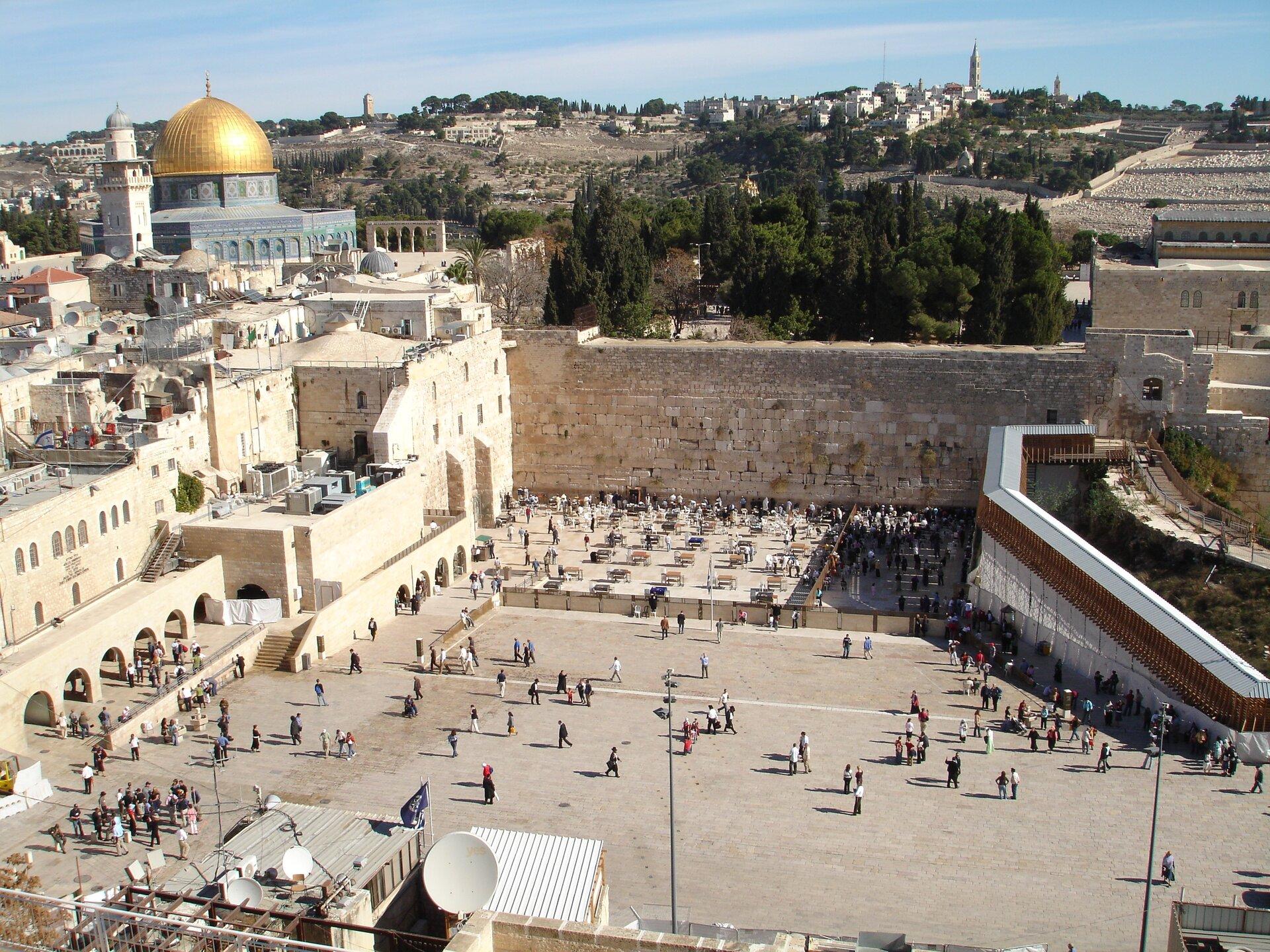 Na zdjęciu duży plac, okalają go budynki, ztyłu kamienna ściana. Na placu wiele osób. Wtle świątynia zkopułami, zabudowania irośliny.