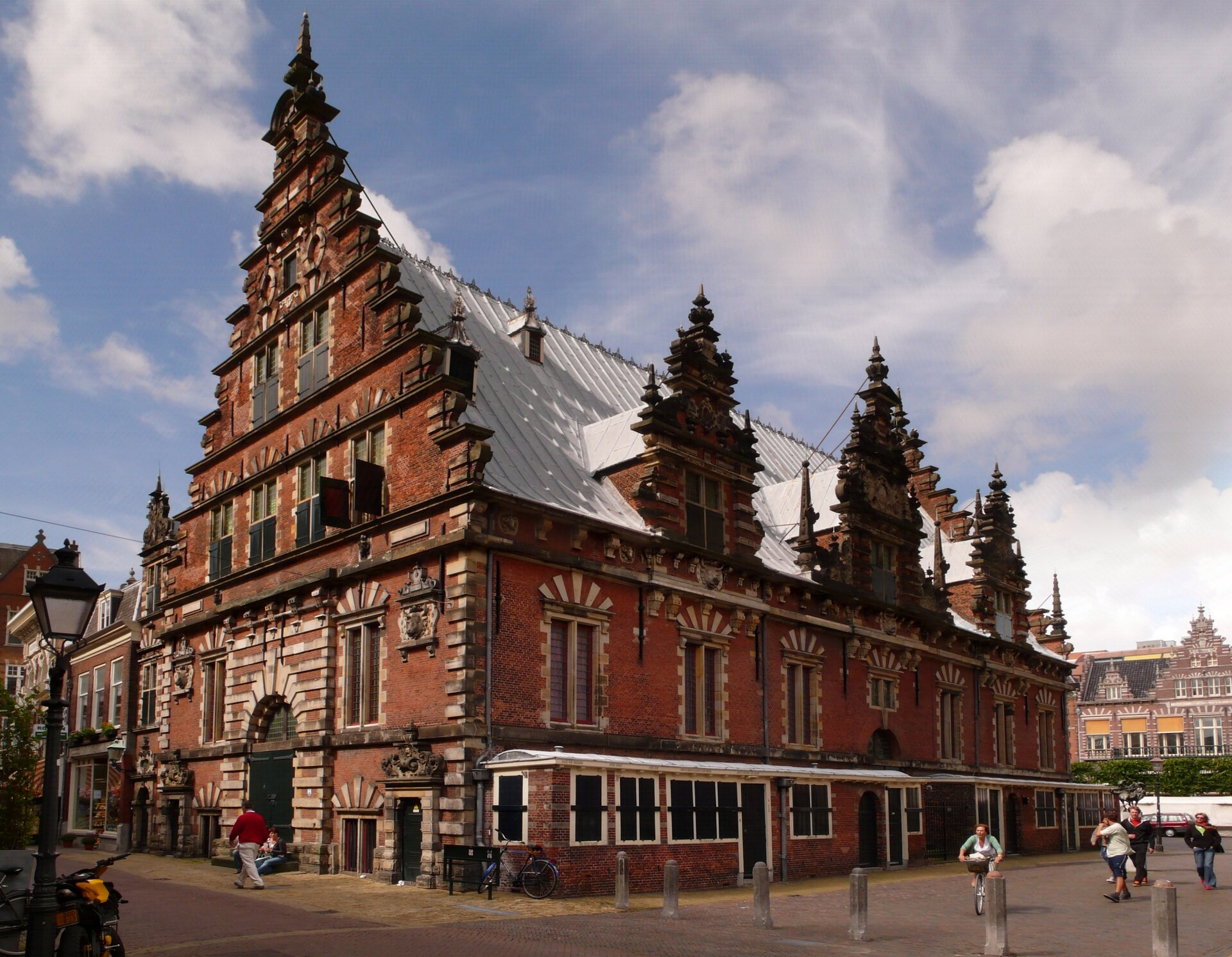 Haarlem – hala targowa (ławy rzeźnicze – jatki) – wybudowana na wielkim Rynku wHaarlemie wlatach 1602-1603.Jestto północna odmiana architektury renesansowej. Zwróć uwagę na materiał, jakim się posłużono do budowy ścian idetalu wykończeniowego; potem na okna, ich akcentowanie, kształt oraz rozmieszczenie, wreszcie na szczyt budynku ijego ozdoby. Haarlem – hala targowa (ławy rzeźnicze – jatki) – wybudowana na wielkim Rynku wHaarlemie wlatach 1602-1603.Jestto północna odmiana architektury renesansowej. Zwróć uwagę na materiał, jakim się posłużono do budowy ścian idetalu wykończeniowego; potem na okna, ich akcentowanie, kształt oraz rozmieszczenie, wreszcie na szczyt budynku ijego ozdoby. Źródło: Welleschik, Wikimedia Commons, licencja: CC BY-SA 3.0.