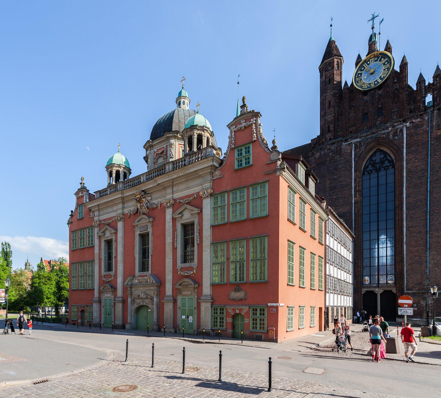 Ilustracja przedstawia barokową Kaplicę Królewską wGdańsku, która powstała wlatach 1678-1681 zinicjatywy gdańskich katolików zpomocą króla Polski Jana III Sobieskiego. Architektem kaplicy był Tylman zGameren. Pierwszą część stanowi budynek oróżowym kolorze elewacji ztrzema wejściami itrzema kopułami. Środkowa kopuła jest wyraźnie większa od bocznych. Prawa część zdjęcia to druga część budynku. Jest wyraźnie wyższa od pierwszej, ana samej górze znajduje się duży zegar ikrzyż. Nad wejściem tej części znajduje się okno ciągnące się wgórę prawie do miejsca gdzie jest zegar.