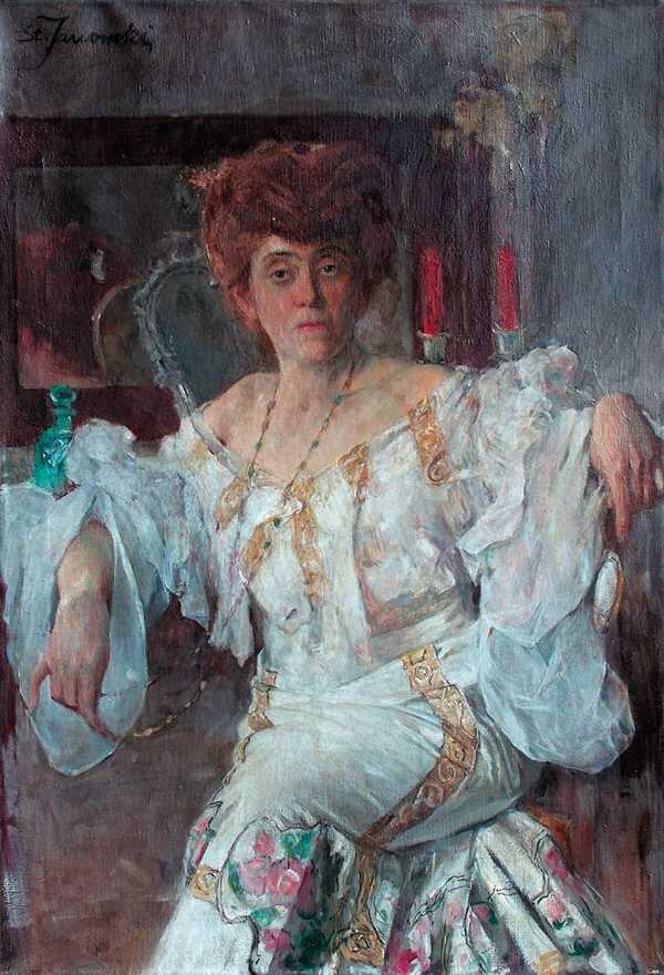 Obraz przedstawia portret kobiety. Jest ona wśrednim wieku. Ma gęste włosy, uczesane starannie. Kobieta siedzi. Ma założoną nogę na nogę. Jej łokcie wspierają się prawdopodobnie na stojących za nią meblach. Kobieta jest ubrana welegancką, bogato zdobioną, długą suknię. Na szyi ma długi naszyjnik. Prawą dłonią trzyma jego koniec. Wtle wisi niewielkie, prostokątne lustro. Odbija się wnim tył głowy kobiety. Po lewej stronie lustra stoi niewielka karafka. Po prawej stronie lustra stoją wlichtarzach dwie świece.