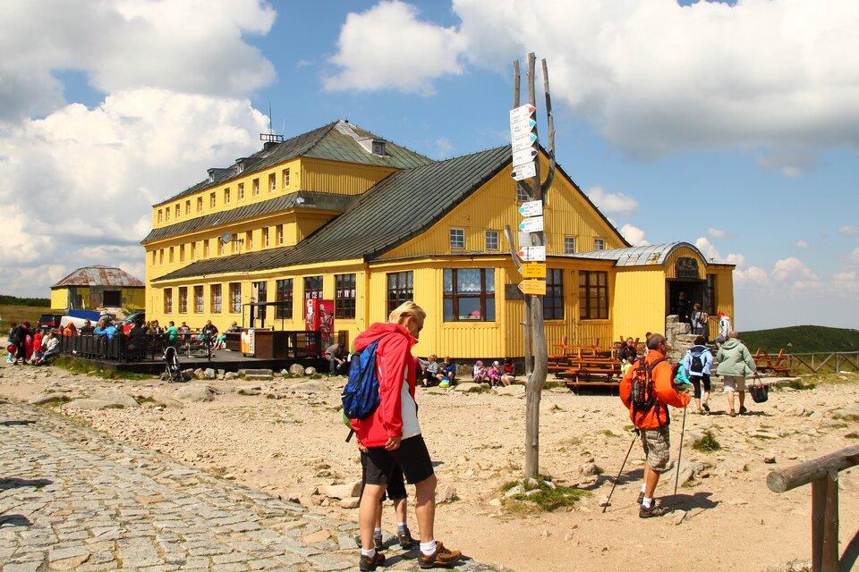 Na zdjęciu żółty budynek ze spadzistym dachem, przed nim turyści.