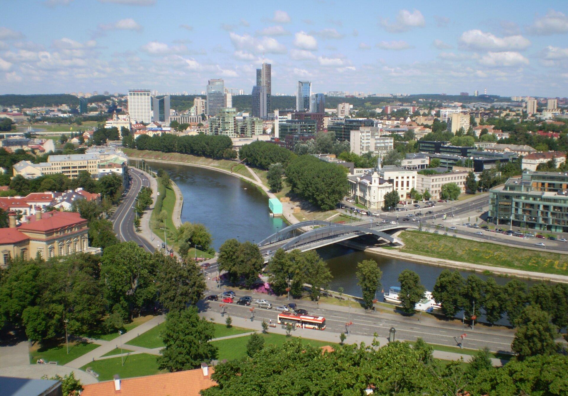 Na zdjęciu nowoczesna zabudowa miejska, wysokie budynki, rzeka, most, ulice.