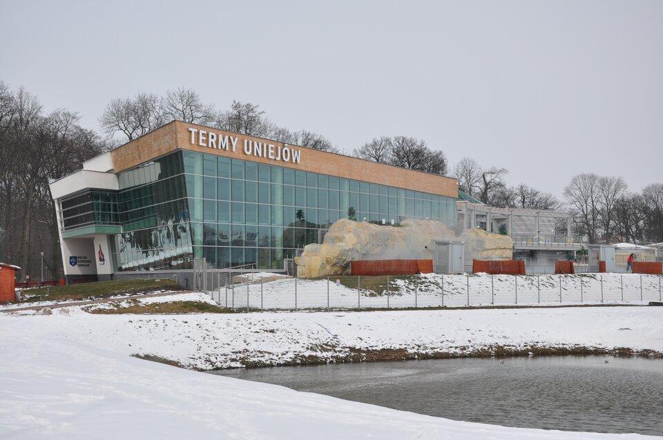 Na zdjęciu nowoczesny budynek, przed nim zbiornik wodny.