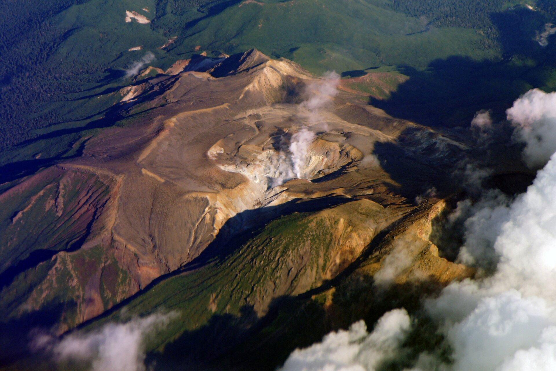 Na zdjęciu widok zgóry na wulkan, zktórego wydobywa się chmura dymu.
