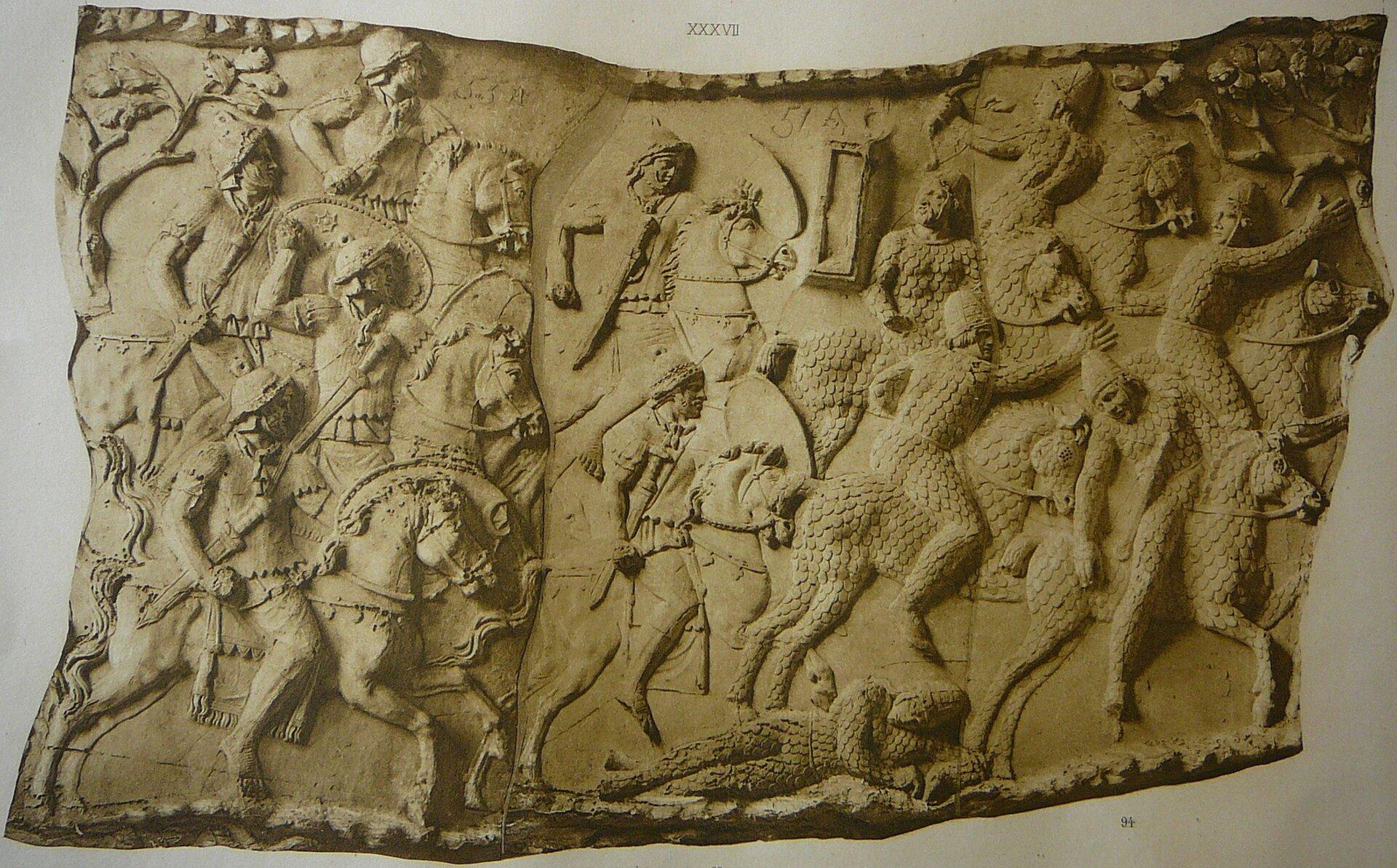 Ilustracja interaktywna przedstawia zdjęcie fragmentu Kolumny Trajana. Ukazuje fragment bitwy Rzymian zDakami. Po lewej stronie na koniach ukazani są Rzymianie, którzy atakują wroga. Wojownicy na koniach ukazani są rzędowo. Prawa strona przedstawia uciekających Daków. Jedni odwracają się, inni spadają zkoni. Na dole leży martwy żołnierz.