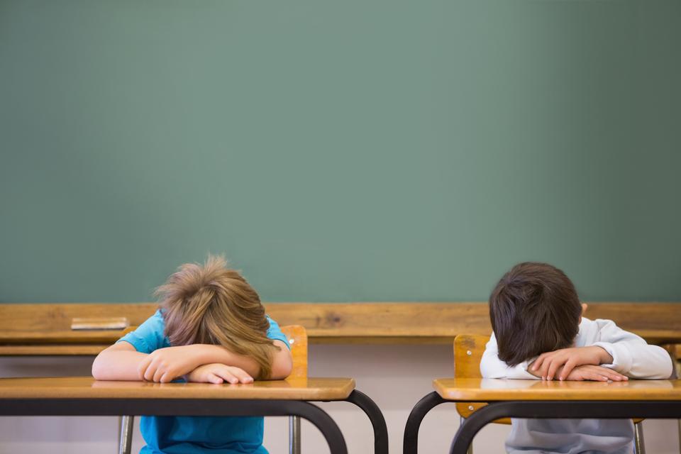 Fotografia przedstawia dwóch chłopców siedzących na krzesłach przy ustawionych obok siebie biurkach, wtle tablica szkolna. Każdy zchłopców położył głowę na ramionach opartych na biurku iodpoczywa.
