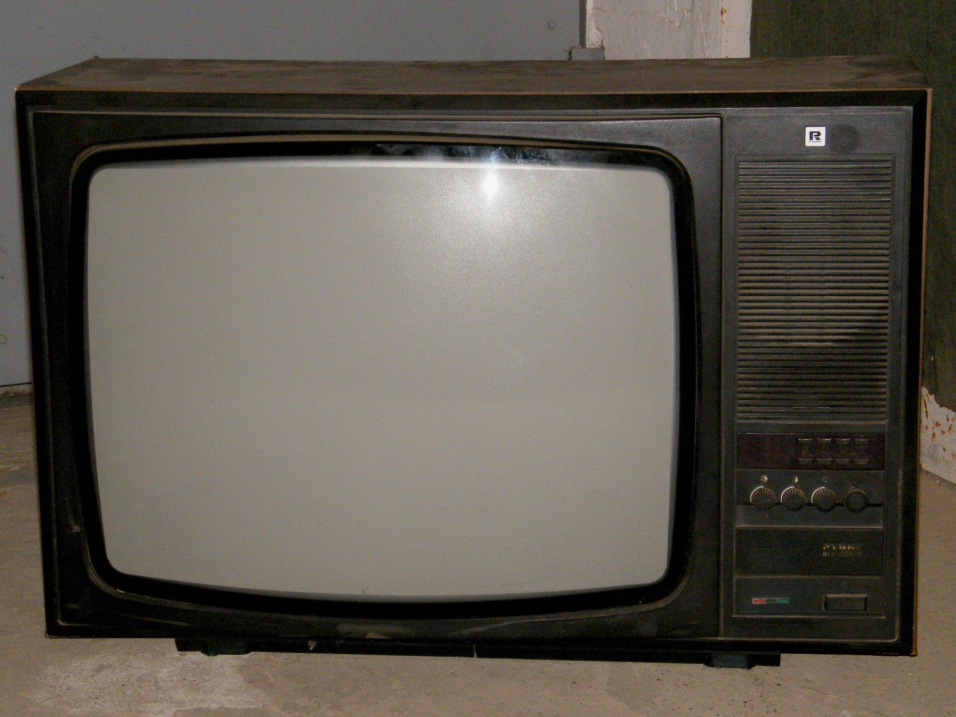 Fotografia barwna przedstawiająca telewizor kolorowy z1975 roku. Duża obudowa iwypukły kineskop.