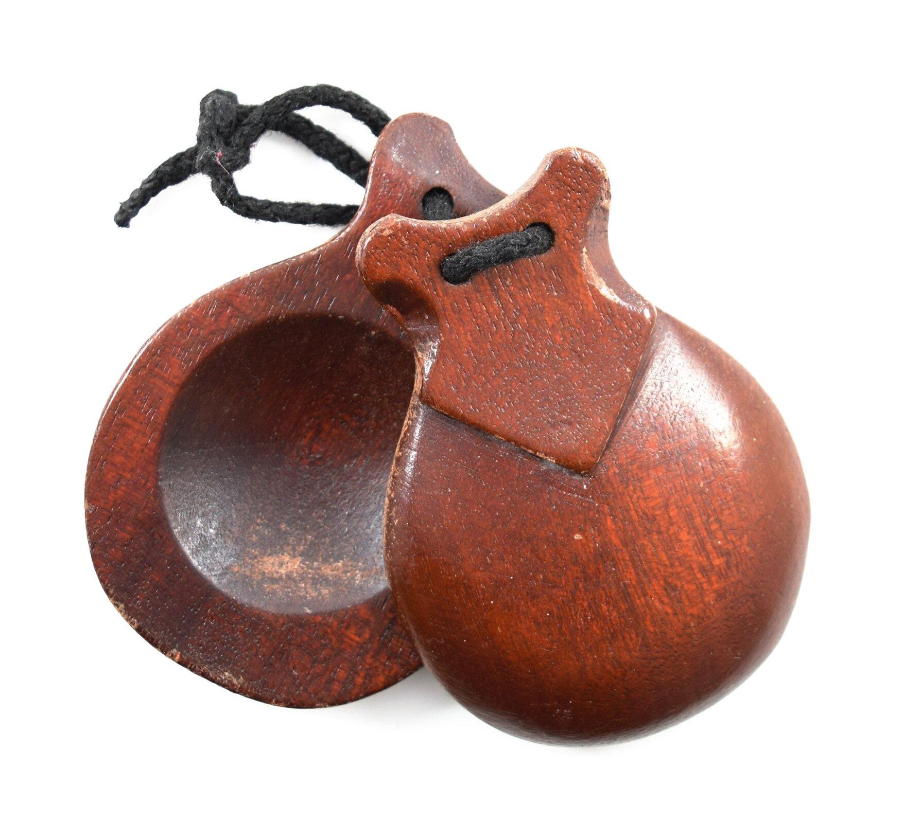 Ilustracja przedstawia kastaniety, instrument muzyczny zgrupy idiofonów zderzanych, składający się zdrewnianej rękojeści, do której przymocowano zjednej lub obu stron pary drewnianych muszelek związanych sznurkiem. Przy potrząsaniu muszelki uderzają wznajdującą się między nimi drewnianą płytkę.