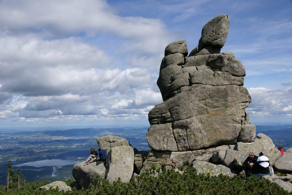 Na zdjęciu forma skalna składająca się zkilku silnie spękanych granitowych ostańców, wdole rozległa równina.