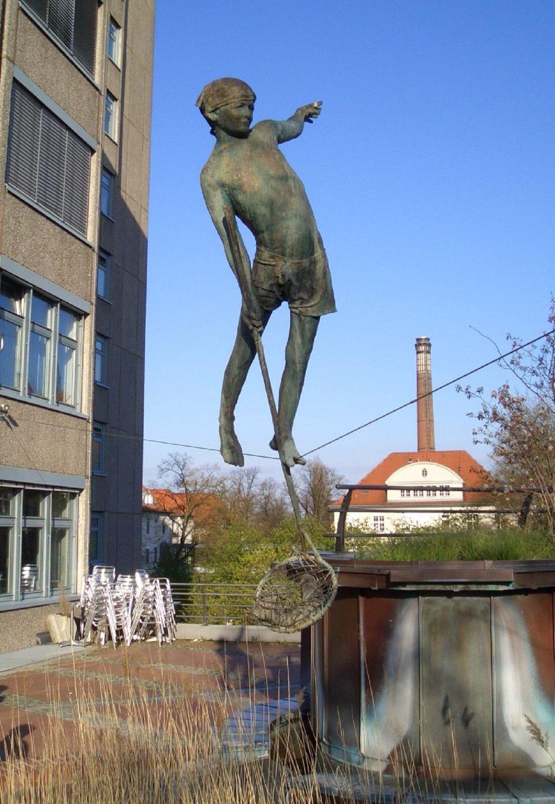 """Ilustracja przedstawia rzeźbę Jerzego Jotki Kędziory pt. """"Mały wędkarz"""". Dzieło przedstawia chłopca przechodzącego po linie nad zbiornikiem wodnym. Chłopiec wjednej ręce trzyma siatkę na ryby, drugą rękę ma wyciągniętą wbok, co pozwala mu na zachowanie równowagi."""