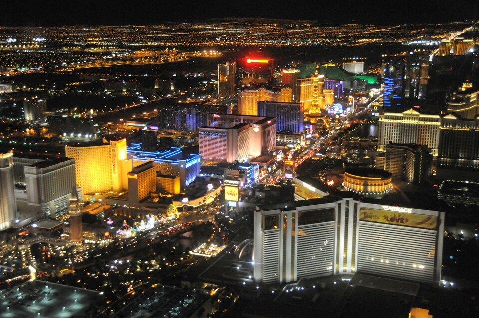 Na zdjęciu nowoczesne miasto wwysoką zabudową wnocy. Kolorowo oświetlone.