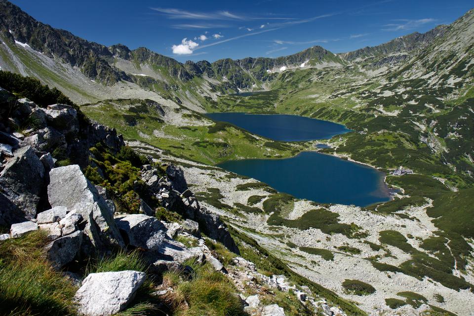 Fotografia przedstawia dwa niebieskie stawy wotoczeniu skał iszczytów gór. To Dolina Pięciu Stawów wTatrzańskim Parku Narodowym.