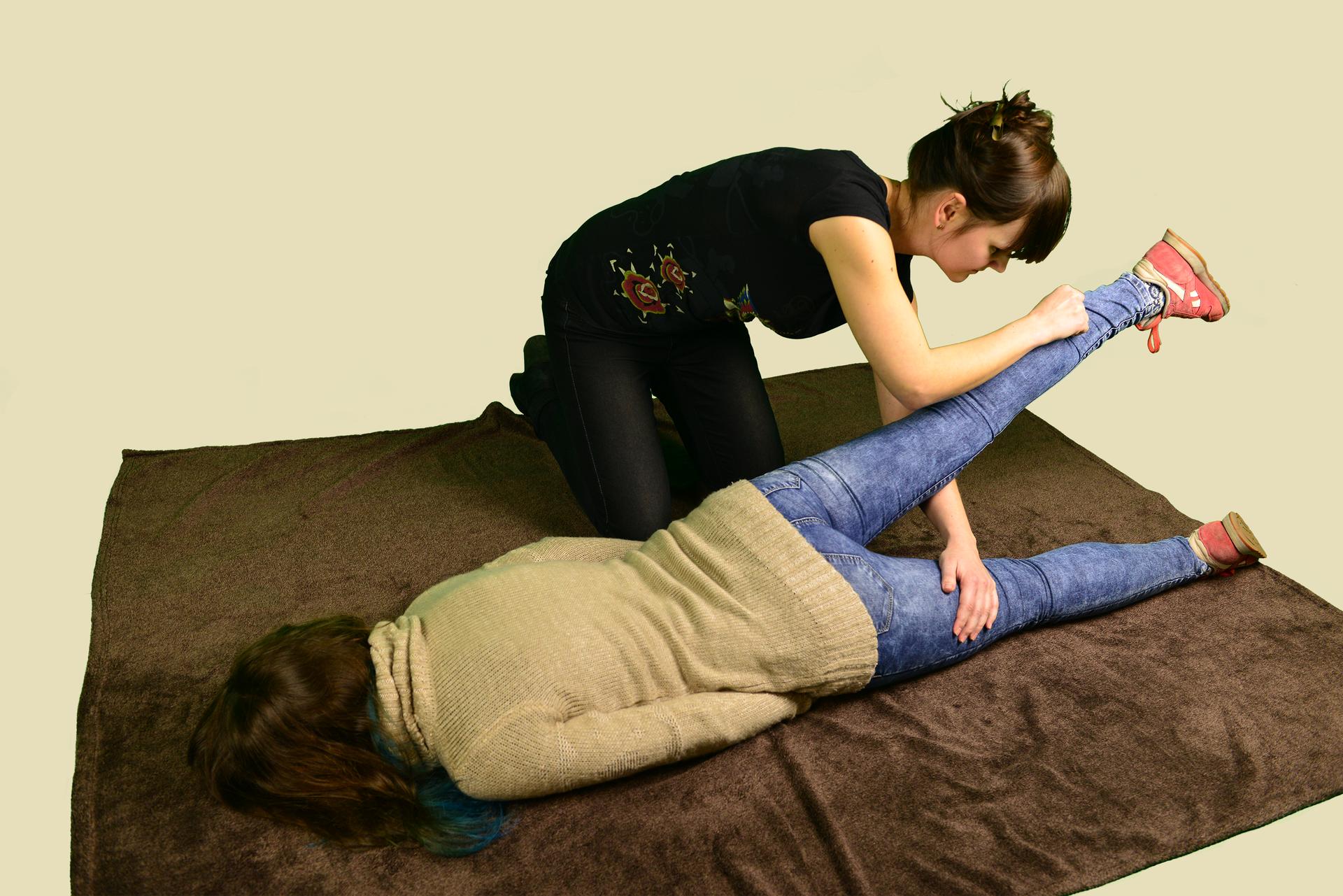 Osoba poszkodowana leży nadal na brzuchu. Dłoń ręki pod biodrem. Kobieta pomagająca osobie poszkodowanej, unosi nogę leżącej. Unoszona noga to noga bliżej kobiety. Druga ręka kobiety przełożona jest poniżej uniesionej nogi osoby leżącej – tak, aby dłoń kobiety była umieszczona poniżej biodra osoby poszkodowanej.