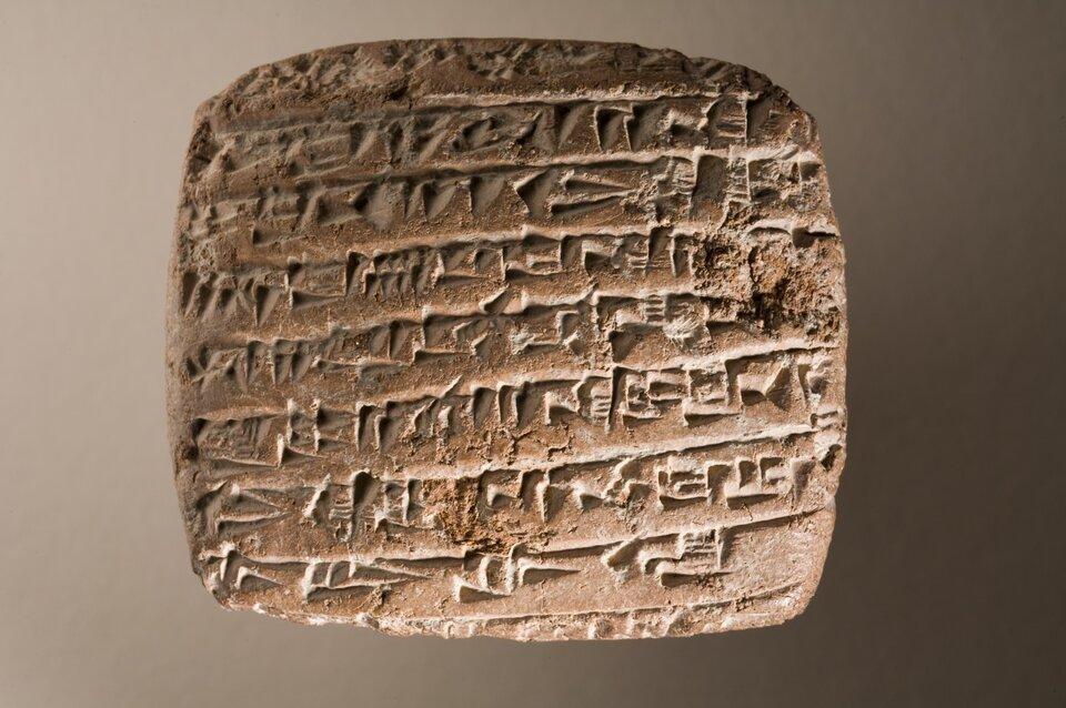 Na zdjęciu kamienna tabliczka zpismem klinowym – zygzakowate znaki.
