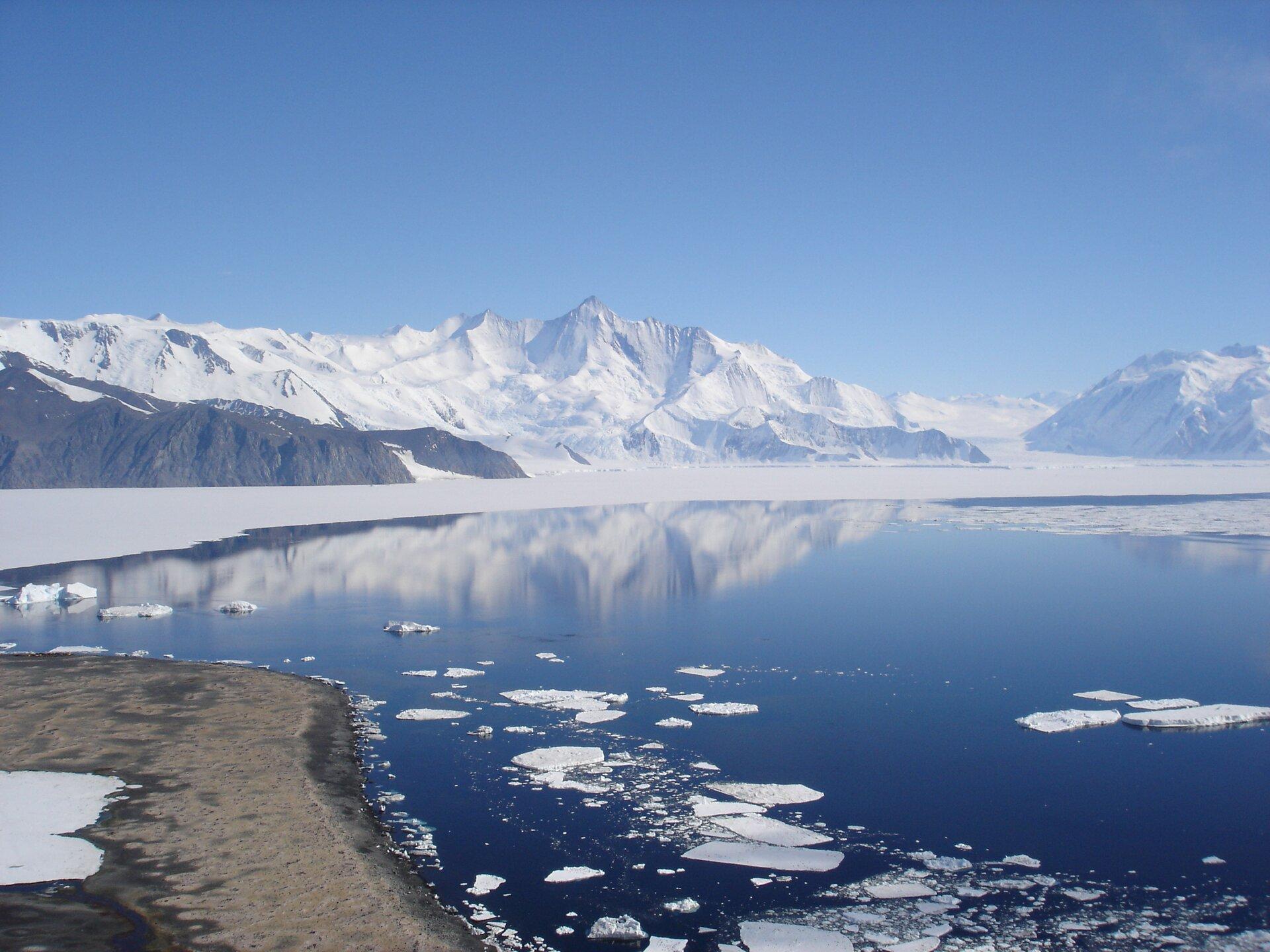 Na ilustracji brzeg morza, piaszczysta plaża, wwodzie kry lodowe, na drugim brzegu ośnieżone góry schodzące do morza.