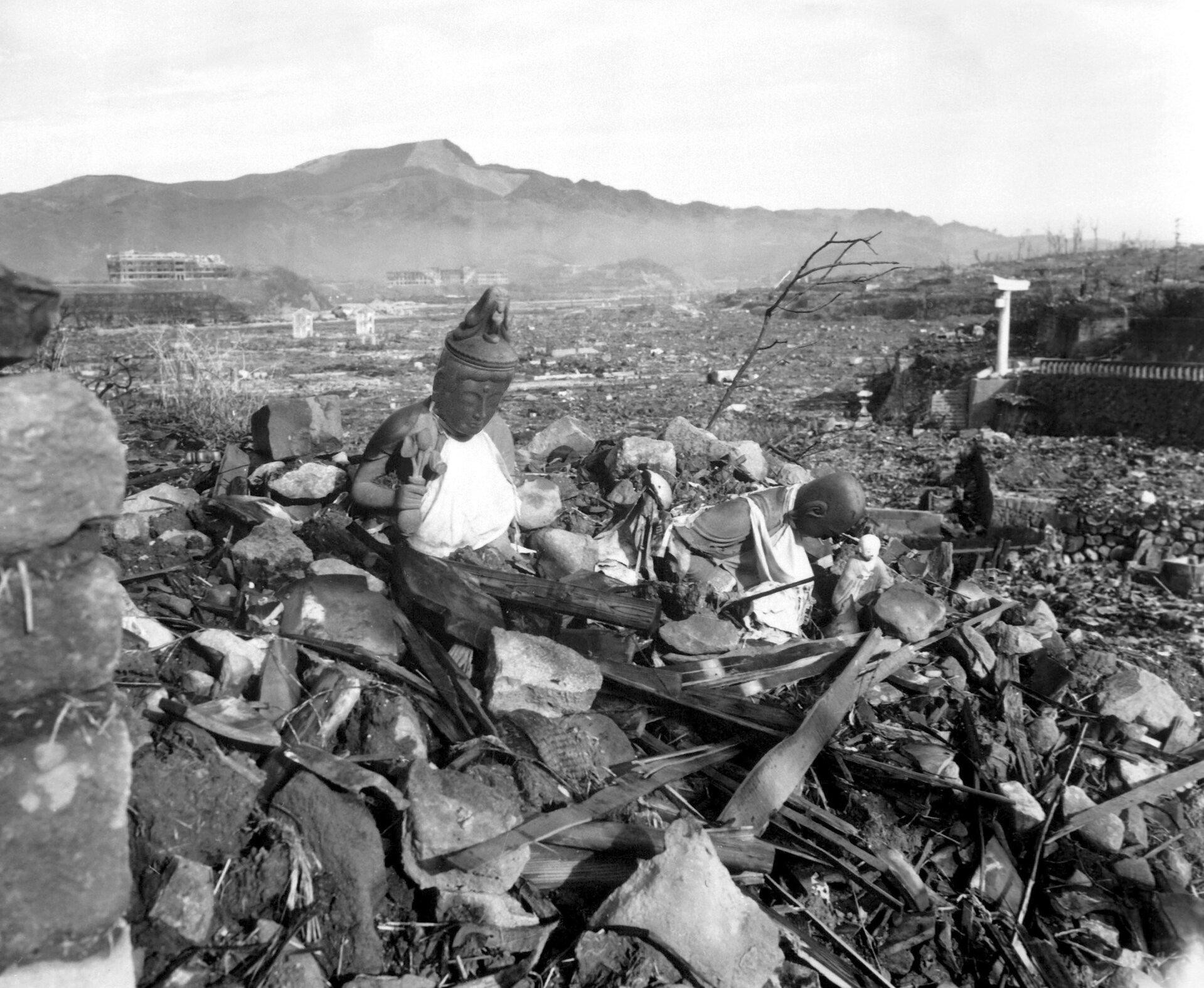 Zdjęcie przedstawia zniszczone przez wybuch bomby atomowej tereny Hiroszimy iNagasaki. Fotografia czarno-biała. Na pierwszym planie widoczne starta gruzów, połamanych desek ikonstrukcji oraz fragment figurki Buddy. Nieco dalej widać ogrom zniszczeń spowodowanych przez wybuch wojny. Prawie wszystko zostało zrównane zziemią. Woddali widać szkielety budynków. Wtle zarys gór.