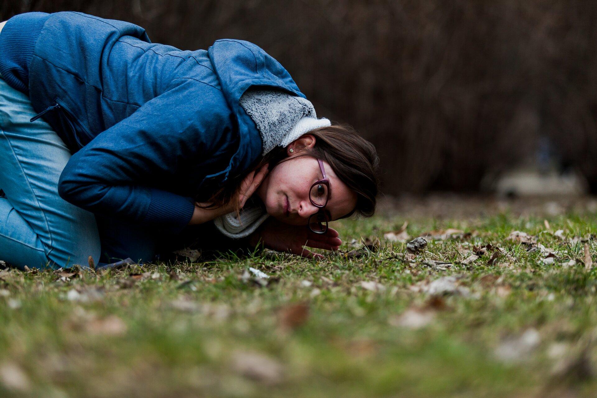 Zdjęcie człowieka nasłuchującego zwierząt zuchem przy ziemi