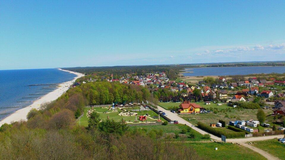 Na zdjęciu widok zgóry na brzeg morski, plażę, teren zabudowany itereny zielone oraz jezioro przybrzeżne wniewielkiej odległości od morza.
