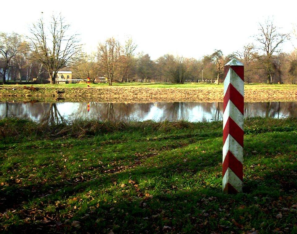 Na zdjęciu rzeka wpłaskim terenie. Na dalszym brzegu słupek wczarno-czerwono-żółte pasy, na bliższym brzegu słupek wbiało-czerwone pasy.