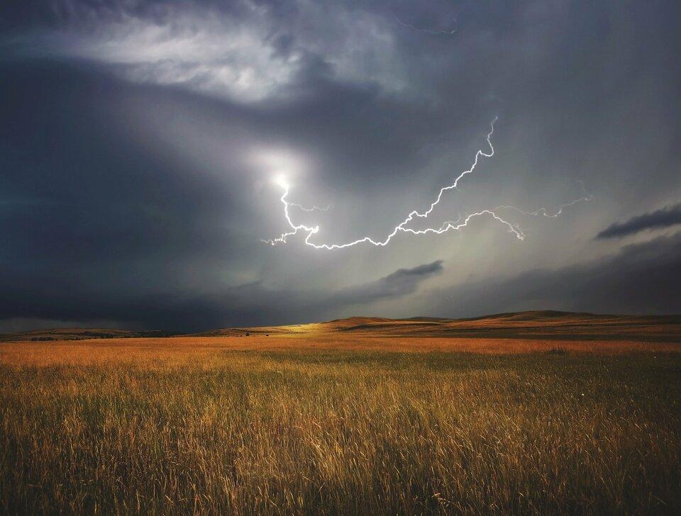 Zdjęcie przedstawia krajobraz podczas burzy zpiorunami. Na pierwszym planie wdolnej części sceny oświetlone ciepłym światłem słonecznym pola zbóż. Wtle niskie wzgórza. Niebo nachmurzone, wchłodnych odcieniach błękitu ifioletu. Wcentralnej części kadru na niebie jasna błyskawica rozszczepiająca się na kilka odnóg.