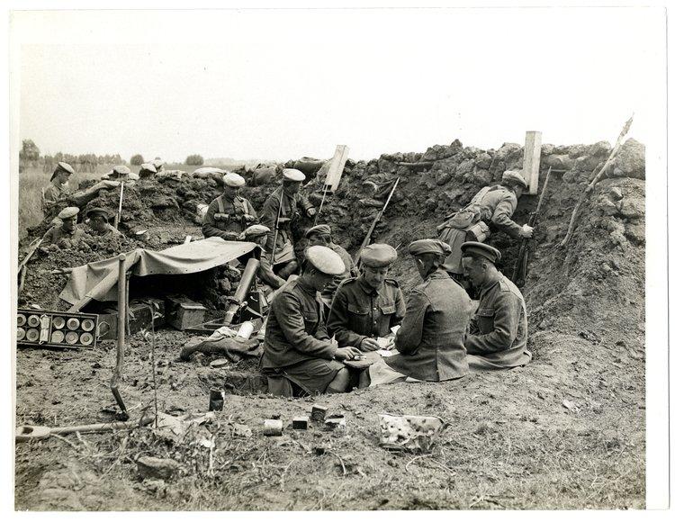 zdjecie przedstawia grupę żołnierzy spędzajacych czas wolny, wtle okopy