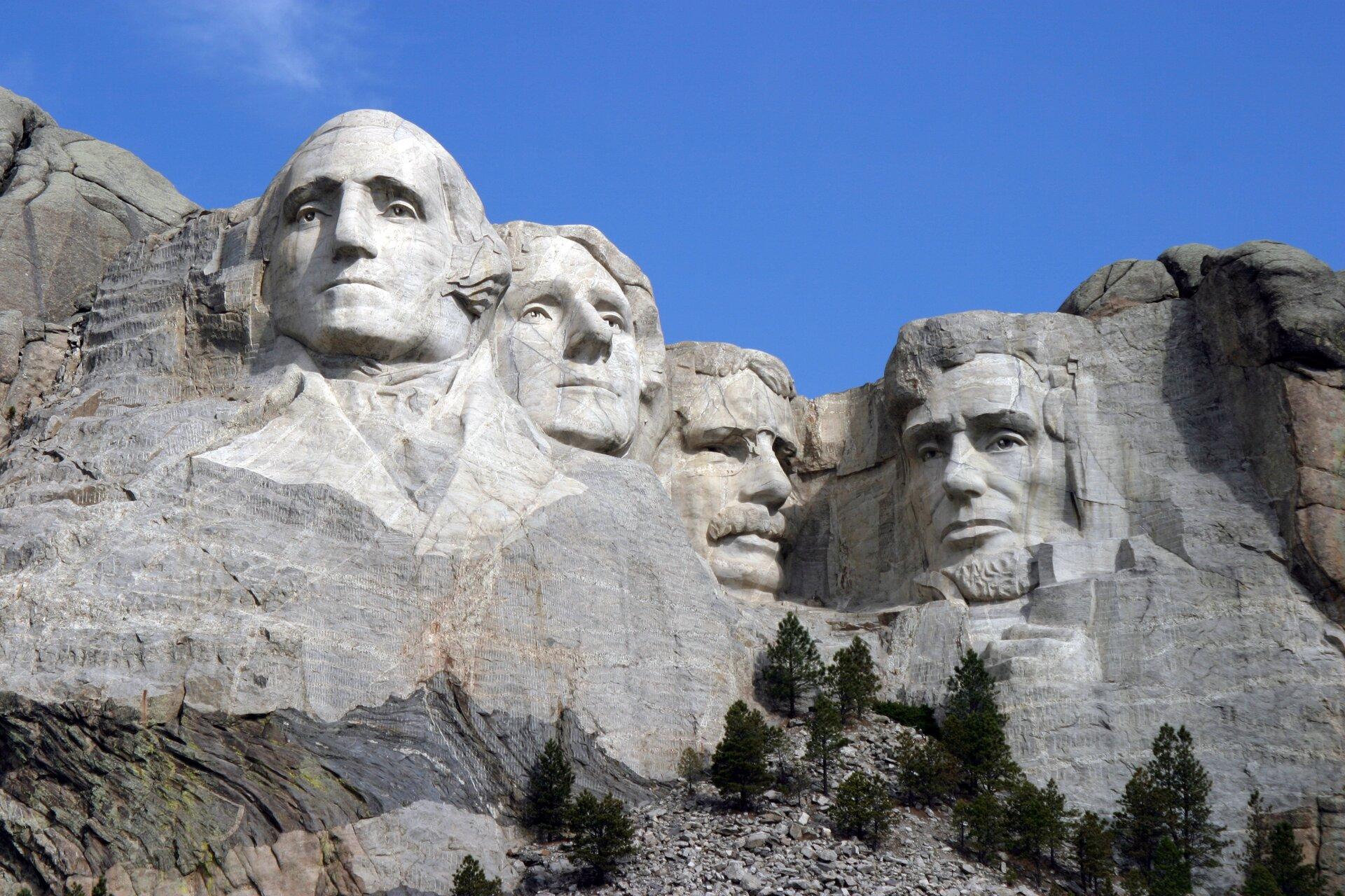 """Ilustracja przedstawia """"Pomnik Mount Rushmore"""" autorstwa Gutzona Borglumy. Ukazuje wykute wskałach głowy czterech prezydentów USA. Od lewej są to: George Washington, Thomas Jefferson, Theodore Roosevelt oraz Abraham Lincoln. Mimika postaci wskazuje na powagę."""