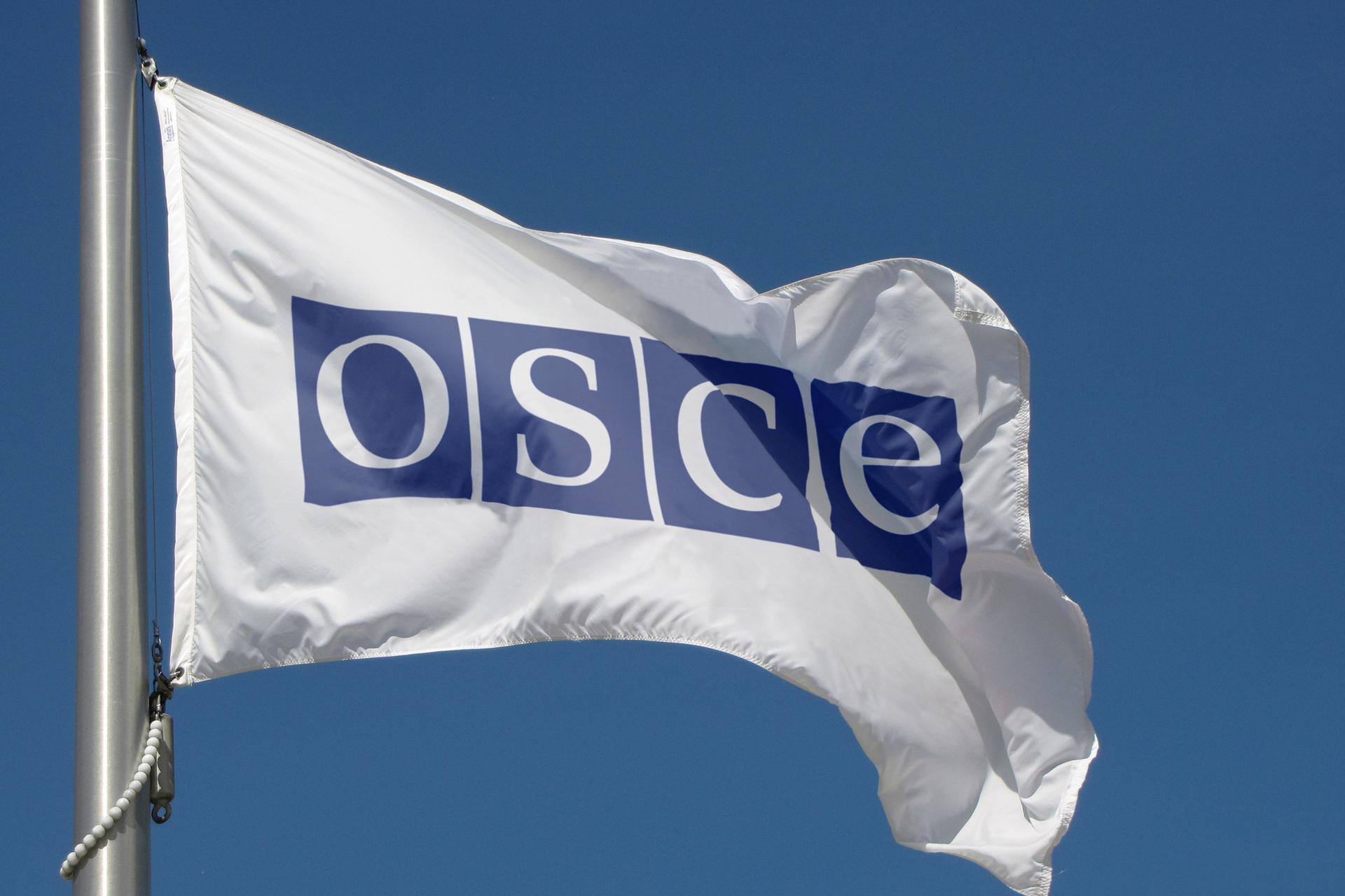 Kolorowe zdjęcie flagi OBWE. Biała prostokątna flaga zawieszona na maszcie. Flaga powiewa wprawą stronę zdjęcia. Na białej powierzchni, na środku flagi, cztery granatowe kwadraty. Kwadraty ułożone wrzędzie. Na każdym jedna biała litera. Od lewej: O, S, C, E.
