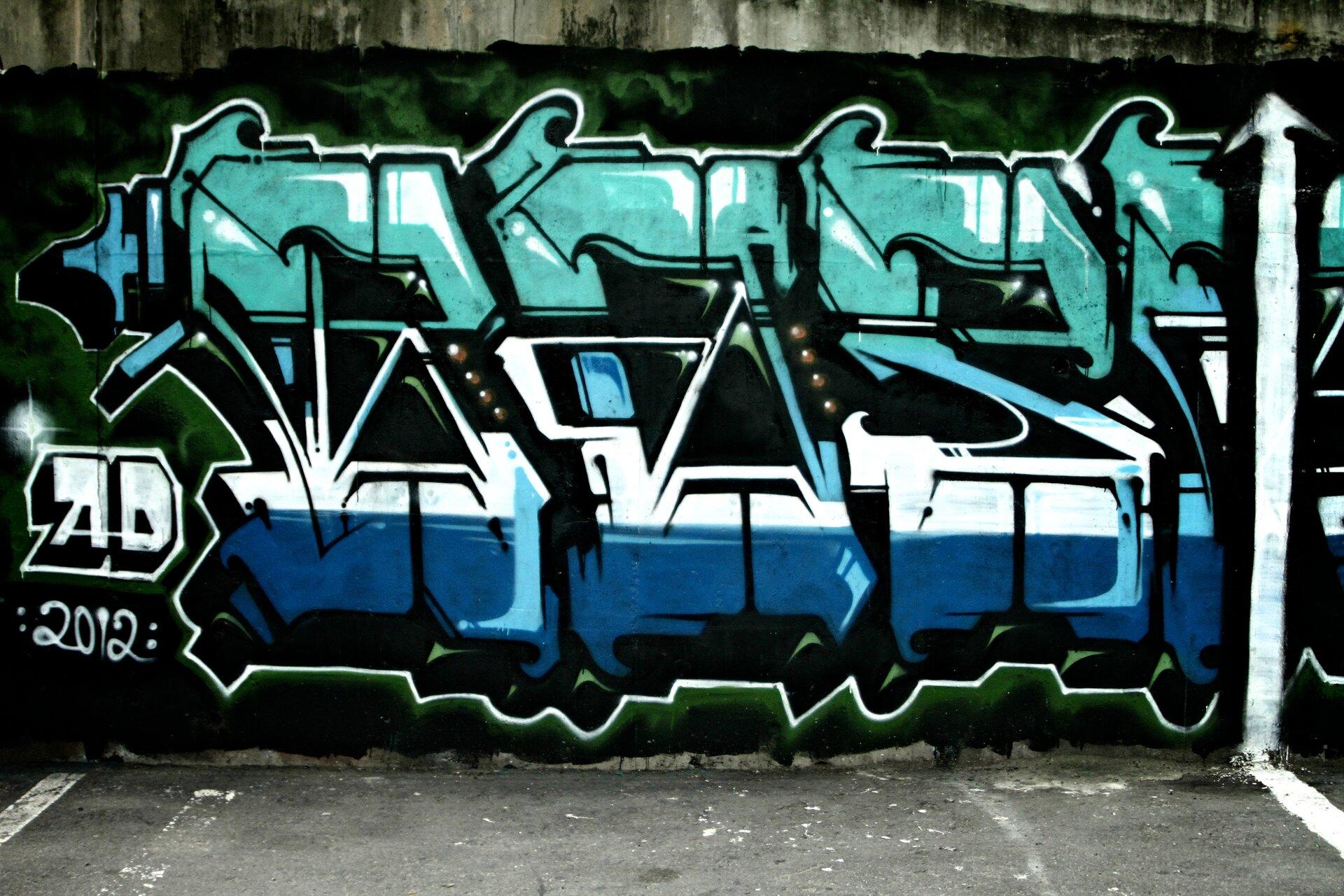 Ilustracja przedstawia napis S.O.S zamieszczony na ścianie. Wykonane jest wkolorach od turkusu, białego, niebieskiego, oraz czarnego. Wlewym dolnym rogu, widnieje podpis: AD 2012.