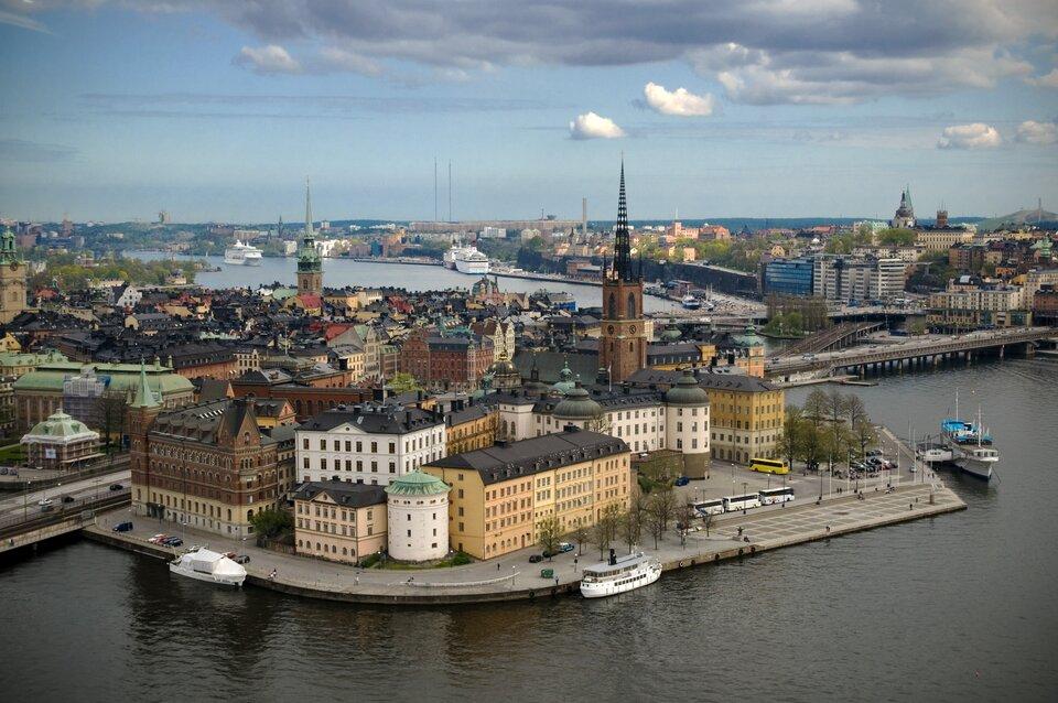 Na zdjęciu zwarta zabudowa miejska, liczne wieże, woddali kominy. Miasto położone nad wodą, mosty, statki.