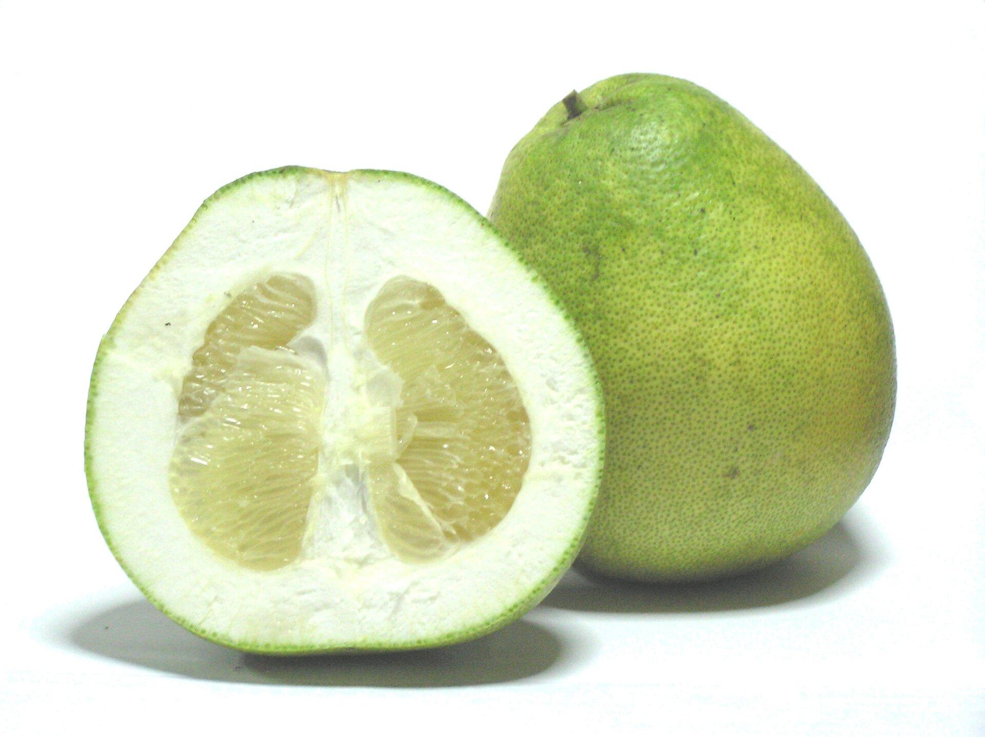Fotografia przedstawia dwa jasnozielone owoce pomelo. Jeden znich jest przekrojony pionowo dla uwidocznienia miąższu.