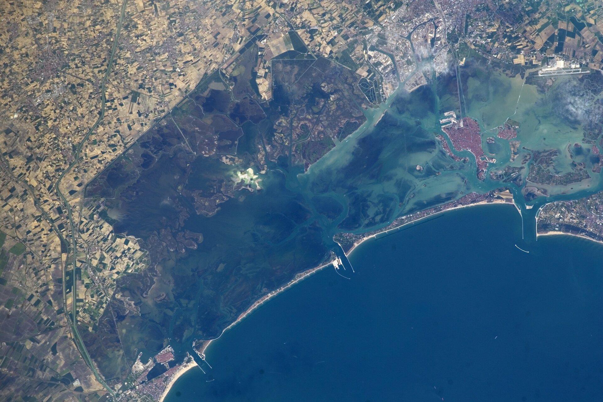 Na zdjęciu wybrzeże lagunowe. Zlewej strony tereny gęsto zabudowane. Równolegle do brzegu piaszczyste wały. Wąski pas morza odcięty od otwartego morza ma kolor jaśniejszy niż otwarte morze, które ma kolor granatowy.