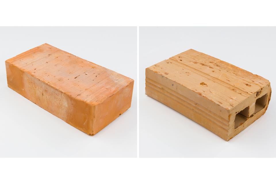 Ilustracja przedstawia dwa różne rodzaje cegieł sfotografowanych wtaki sam sposób, wrzucie izometrycznym, czyli nieco zgóry, pod kątem 45 stopni do ich ścianek bocznych. Oba zdjęcia przedstawiają cegły na takim samym, pustym białym tle. Cegła zlewej strony ma barwię intensywnie pomarańczową ijest jednolita. Cegła zprawej strony ma barwę mniej nasyconą ima dwie dziury okwadratowym przekroju ciągnące się przez całą długość. Jest to tak zwana cegła dziurawka.