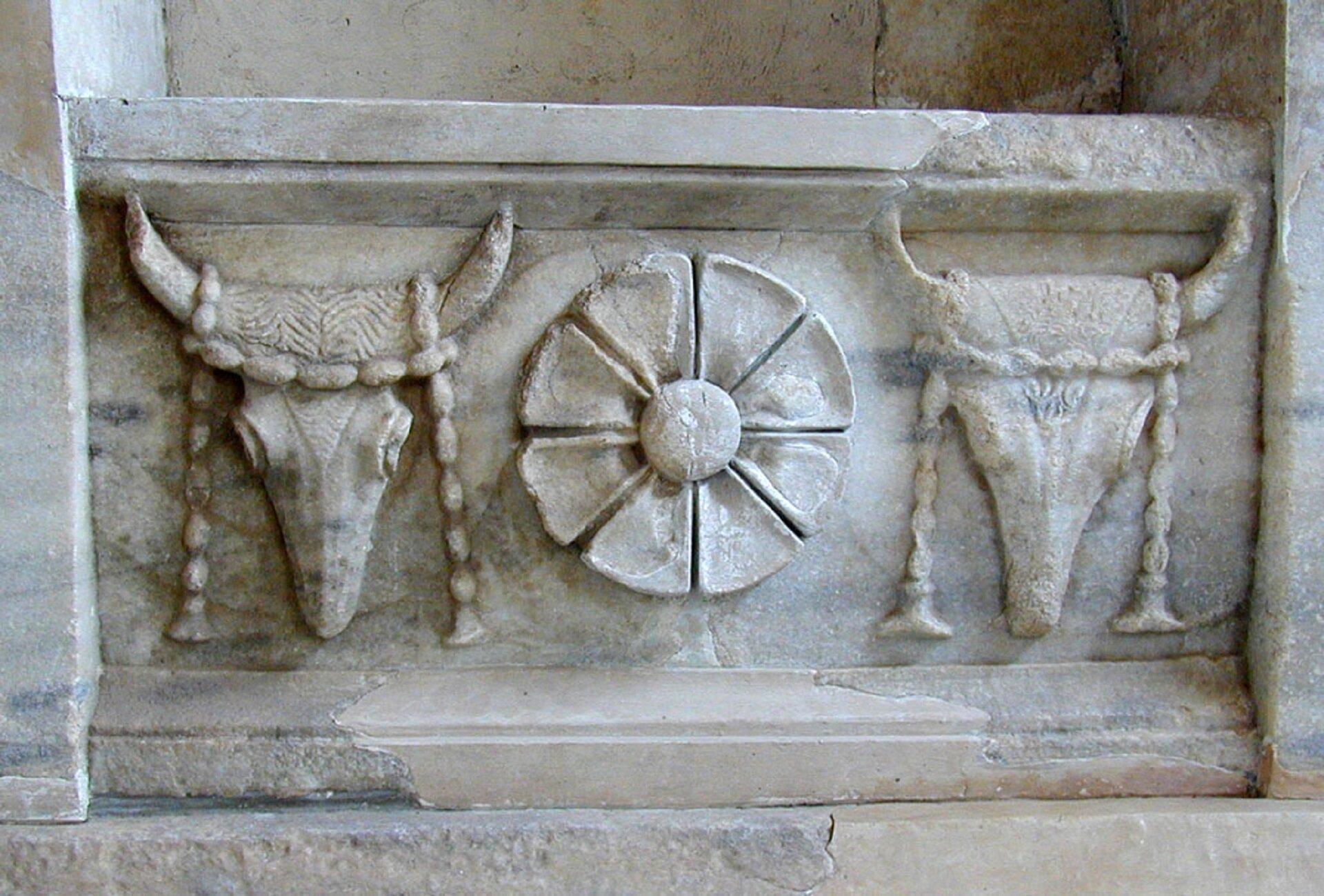 Ilustracja przedstawiająca ornament – bukranion. Na fotografii widoczne są trzy elementy. Po środku znajduje się dekoracja podobna do kwiatu, po obu jej stronach można zobaczyć głowy zwierząt zrogami isznurkiem, co może złudnie przypominać hełmy wikingów.