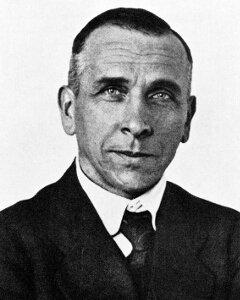 Na zdjęciu Alfred Wegener. Mężczyzna wśrednim wieku. Sylwetka od ramion wgórę. Ciemne, krótkie włosy, zaczesane do tyłu. Ubrany wgarnitur, białą koszulę ikrawat.