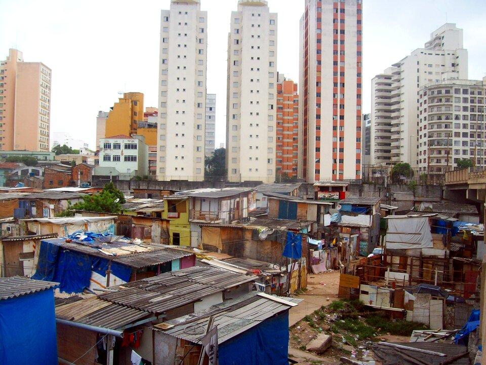 Na zdjęciu dzielnica mieszkaniowa wSao Paulo. Na pierwszym planie favela zprowizorycznymi domami. Domy zbudowane znajtańszych materiałów: tektury, dykty, blachy, desek. Wtle wieżowce.