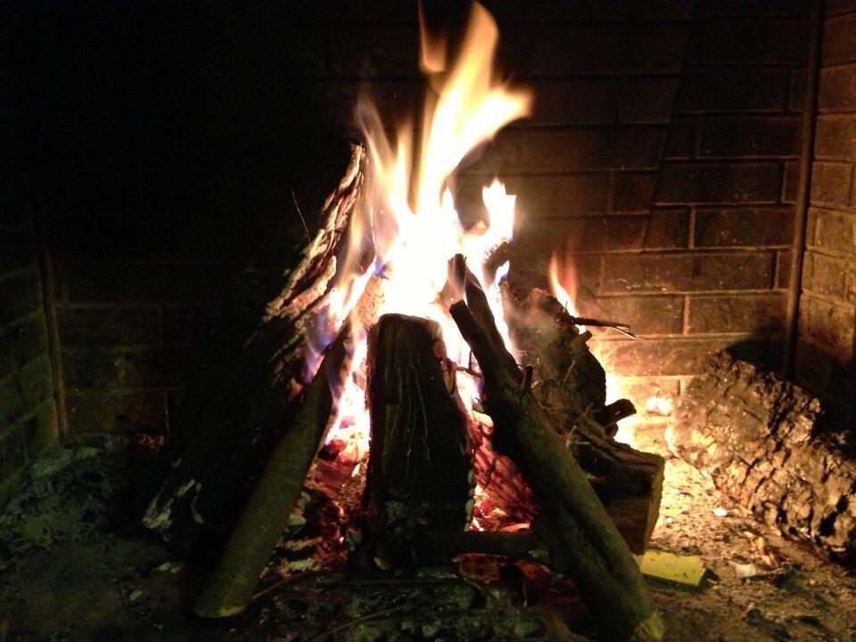 Fotografia pokazuje kominek zpalącymi się jasnym płomieniem polanami drewna.
