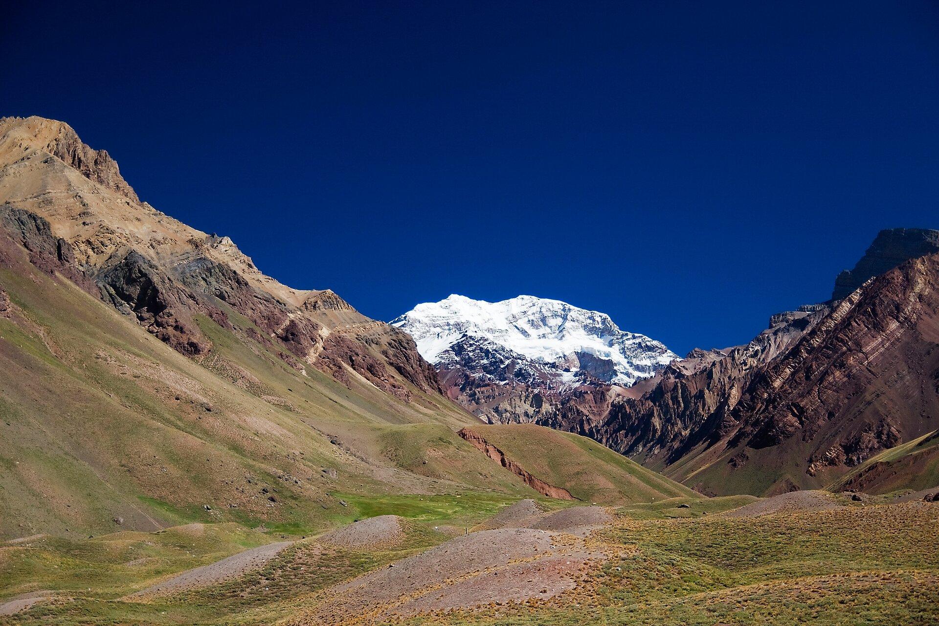 Na zdjęciu wysoki, skalisty szczyt pokryty wgórnej części śniegiem. Na pierwszym planie inne szczyty, nieośnieżone, wdolinie uboga roślinność trawiasta.