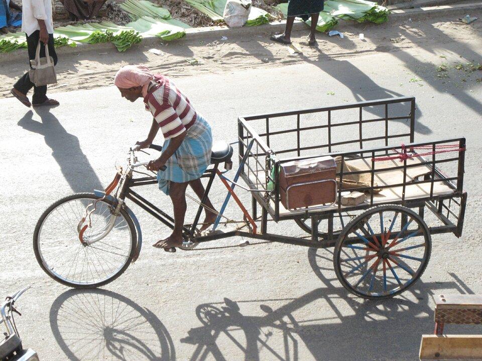 Na zdjęciu bosy ciemnoskóry rowerzysta jedzie specjalnym rowerem. Zamiast jednego koła ztyłu rower ma dwa koła, na nich rodzaj okratowanej ze wszystkich boków platformy do przewożenia towarów. Na poboczu drogi przechodnie.