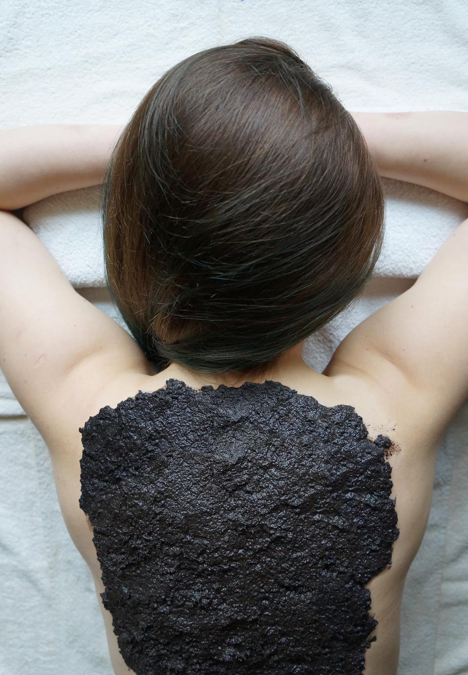 Fotografia przedstawia kobietę zdługimi ciemnymi włosami podczas zabiegu leczniczego. Leży na brzuchu zrękami pod brodą. Skóra jej pleców jest pokryta ciemna masą, czyli borowiną, pochodzącą ztorfu. Wten sposób leczy się stany zapalne ichoroby mięśni istawów.